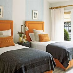 A bold color scheme of orange, dark gray, and pale blue for the guest room.