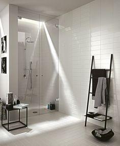 salle de bain blanche décorée d'un carrelage rectangulaire et carré blanc et aménagée avec une table d'appoint et un porte-serviettes échelle en noir