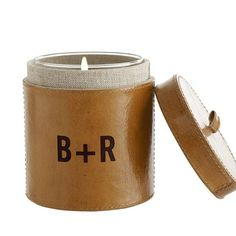 This leather wrapped candleholder has exposed stitching and holds an unscented candle in a glass container.