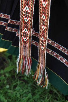 Ullbånd; smale grindvevsband langs kanten, breie fangband rundt livet og hengande ned i fanget. Sunnfjordbunad, Norwegian bunad, traditional folk costume
