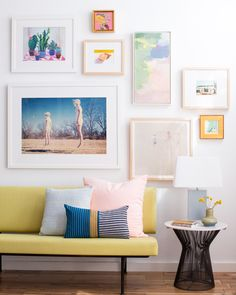 Pastel-colored gallery wall in living room with like-colored pillows and yellow sofa