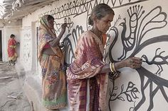 A photograph of two Adivasis painting a Khovar mural