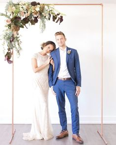 A simple and glam wedding day look, complete with a copper wedding arch. The lovely bride is wearing a cap sleeved, detailed wedding dress with a simple updo while the handsome groom is wearing a blue suit and a rustic boutonniere.   #copper #weddingarch #ceremony #couple #bluewedding | Shine Events AZ | Malone Sinclaire | The Clayton on the Park | Event Rents AZ | Lace and a Barn | Sarahs Garden Style | Wedding Belles AZ | Makia J Beauty | Morilee Official | Sena Nasser | Nick Witherill Simple Wedding Arch, Wedding Arch Rustic, Copper Wedding, Garden Wedding Dresses, Best Wedding Dresses, Trendy Wedding, Dress Wedding, Garden Weddings, Before Wedding
