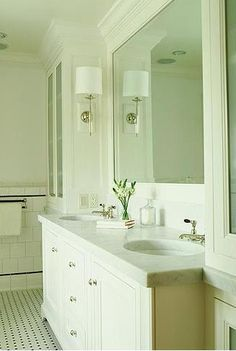 Gorgeous white bathroom; white inset cabinets, uppers with sconces on the sides (vs. in mirrors), marble counters