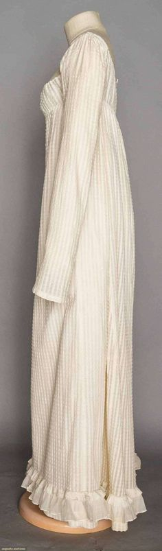 """WHITE COTTON DAY DRESS, 1800-1810  Lot: 8 November 11, 2015 NYC New York City Raised dot textured & striped woven fabric, very high empire bodice, square F neckline, 2 draw-string CB ties, long sleeves, very fine cotton mull double ruffle at hem edge, L 51"""", (minor stains, very small holes & 2 mends on bottom F) very good."""