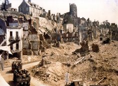 GIs moving through the destroyed city of Saint-Lô, 1944