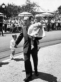 Walt Disney carries Tammy as he leads Christopher through Disneyland