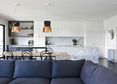 navy sofa + wood table + bentwood chairs + marble island + copper pendants + white cabinetry