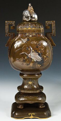 "An elegant bronze multi-tiered and multi-metal covered urn with archaic handles. On its silver-lined lid, bordered by applied silver and gold sprays, a regal silver, shakudo, bronze and gilt finial of the Buddhist divinity, Fugen Bosatsu sits upon his elephant. On one panel in high relief is a family of cranes among fruiting branches; on the other, sprays of kiku. Hakuho sai gold signature. Height, 12.5"". Meiji Period."