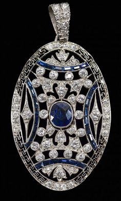 Ladies' Art Deco period 18k white gold (tested, not marked) oval pendant with central bezel set oval standard brilliant cut natural blue sapphire (approx. weight .78 ct), 28 baguette cut blue sapphires and 59 round cut diamonds