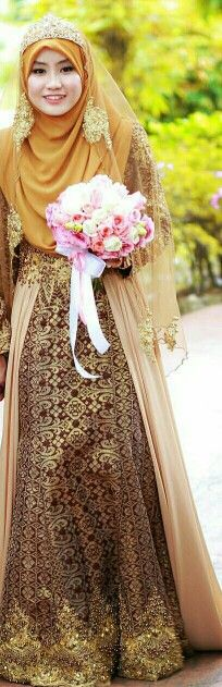 This lovely bride is wearing a Songket wedding gown with hijab.