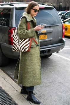 A zebra printed tote is worn with a moss nubby coat and rain booties