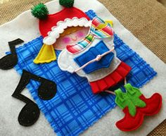 "Cute little caroler #quiet book page in the PDF PATTERN Kool Kids. She is 1 of 8 kids celebrating 8 different holiday events. (love her pleated ribbon skirt and cowboys boots!) With 3 removeable clothing items per kid, the possibilities for creative ""outfit design"" is endless! LindyJ Design at Etsy."