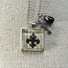 Fleur de Lis  Glass Pendant Necklace with Charm by What The Buckle