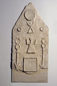 An ancient Phonecian limestone votive stela; decoration in low flat relief; in pediment is a 12 petalled rosette in a disk; 4 line neo-Punic inscription; symbol of the goddess Tanit is flanked by caducei; above them are astral symbols. (British Museum)