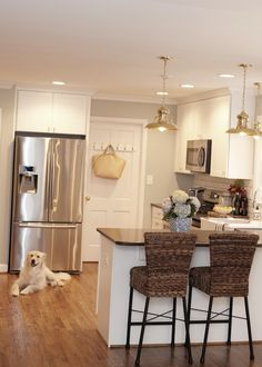 Jessie Epley - Beautiful kitchen features vintage barn pendant over kitchen peninsula lined with seagrass barstools. Kitchen features white shaker cabinets paired with gray countertops and subway tile backsplash with gray grout. Kitchen with microwave above stove and cabinets above double door refrigerato