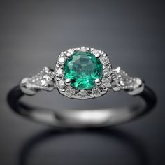 The Perfect Emerald for an Engagement ring, Lots of life transparency and incredible color. 18kt white gold setting with a high quality natural Colombian Green Emerald. weighing .46ct Ring consist on a Cushion style Halo with 12 round brilliant diamonds around the top with a diameter of 1.15 mm each diamond On the shank is adorned with 2 small diamonds of 1.5mm 1 on each side All the diamonds are G-VS with a total weight of .12ct The Colombian Emerald is Conflict Free I picked it myself in…