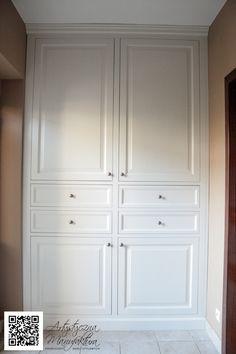 Szafa do zabudowy w stylu angielskim, z pełnymi drzwiami, biała, idealnie pasowana do wnęki. Budowa ramowa, wnętrze z drewnianymi szufladami.