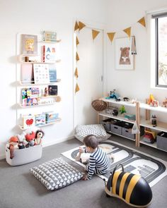 This play room is open and airy, with the use of white shelving and storage. Pops of colour are brought in with the kids decor. I love book shelves on the wall for a kids reading corner.