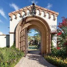 Iron gate framed by cantera arches leading to a courtyard....