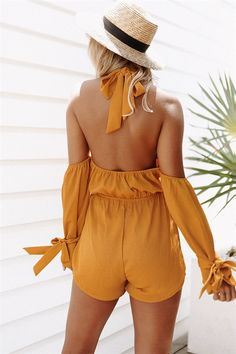 Stand out in the Indra Mustard Playsuit, made from a crepe feel fabric in a bold mustard hue. It is a flattering cold shoulder style and features a high halter neck, full length sleeves with ties at wrists, elasticated waistband and matching waist tie. Complete the look with a tan belt and flats! By Sabo Skirt.