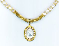 Enchanted Beads created this beautiful, classy bridal necklace with a 18 mm x 14 mm white cameo piece surrounded by small 3mm pearls and framed in a raw brass rope with Cameo Pendant.  The necklace strand is made up of 11/0 metallic gold seed beads and 6mm real pearls. A real beauty!