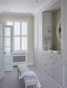 Cottage closet features gray built-in cabinets flanking a gray built-in dresser under a white oval mirror alongside a blue French bench.