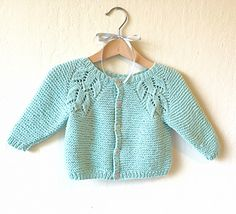 "Knit pattern for a feminine baby cardigan in garter st with a lovely lace ""flower raglan""."