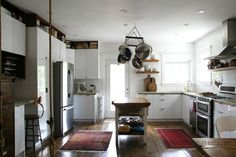 rustic modern ikea kitchen - subway tile, concrete coutertops, butcher block island, pot rack over island in lieu of pendant lighting, vintage rugs, wood open shelving, cutting boards