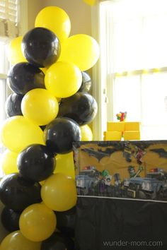 LEGO batman party decorations and ideas.  I love balloon pillars!!  They work with any party theme - like this yellow and black balloon Gotham City balloon pillar for a batman party!  Find the balloons and LEGO Batman tablecloth @Walmart #ad