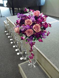 Purple pedestals for stage or steps with roses, orchids and stock