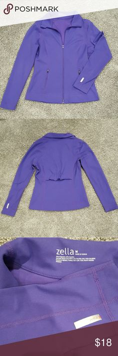 """Zella Purple Performance Jacket Zella performamce jacket in a gorgeous purple. Fitted style with adorable ruffle detail on back. Part under ruffle is open and covering a mesh panel that allows for greater air circulation. Zippers on outside pockets - also has two inner pockets right behind the front pockets.  Zipper has a few chips in the paint noticeable when closely examinating. Otherwise great condition.  88% polyester, 12% spandex. Machine wash.  Approx. 25"""" length, 18"""" bust, 32"""" sleeve…"""