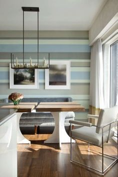 Striped accent wall in dining room done with soothing shades brown and blue. Designer Frank Roop used hand-cut strips of paper-backed silk to create the look, but could be done with paint as well. From Room Lust.