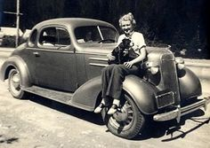 1930s lady wearing trousers and saddle shoes and holding her Pit Bull, all while posing on the fender skirt of a fancy car!