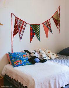 Quarto de criança montessoriano com bandeirolas de tecidos coloridas.