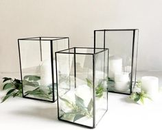 Set of 3 Glass Hurricane Candle Holders Wedding Collection of Large Glass Candle Holders Set of 3 Modern Glass Candle Holders whitecandleswedding Perfect Modern Decor Centrepieces Pillar candles and surrounded by greenery and white roses Perfect Table Decoration Wedding, Modern Wedding Centerpieces, Candle Centerpieces, Wedding Flower Arrangements, Centerpiece Decorations, Pillar Candles, Black Wedding Decor, Centrepiece Wedding, Centerpiece Flowers