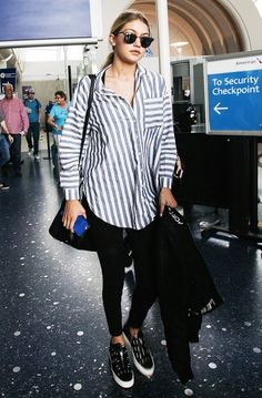 Gigi Hadid wears a striped oversized button-down shirt, leggings, platform sneakers, and Ray-Ban sunglasses