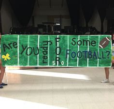 """Are You Ready For Some Football?: GAME DAY/RALLY POSTER:  white poster paper painted green; white yard lines painted on top of green, 50 outlined in gold glitter for added definition; """"FOOTBALL"""" painted in blue for school colors and inside of letters lined with glitter for added definition; Gold Bow also lined with a blue&gold glitter mix."""