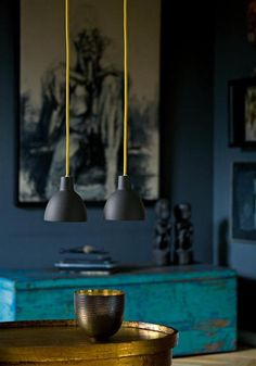 gold, teal, and blue-grey palette - Pendant lights with a pop on neon give a little lift to this space and tie in the brassy colour of that side table.