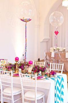 Centros de mesa con globos transparentes de látex rellenos de confeti.