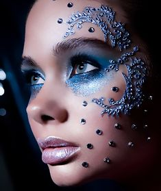 Intricate crystal scrolls and jewels accent a blue glitter eye and frosted lips.