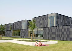 A stack of ceramic-clad boxes forms this monolithic swimming pool complex in the Netherlands.