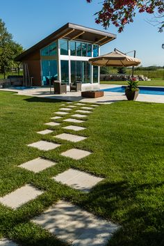 A fantastic pool deck created using Travertine tile, which works perfectly with the modern pool house.