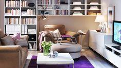 """Einheitlich verwahrt; ein Wohnzimmer mit TIDAFORS 2er-Sofa, TIDAFORS Sessel und TIDAFORS Hocker mit Bezug """"Edsken"""" in Beige, weisses BESTÅ Regal und BESTÅ Ablagebänke in Weiss als Wandregale, KLUBBO Couchtisch in Weiss und kurzflorigem ALMSTED Teppich in Lila"""