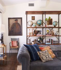 A vintage globe collection, artfully mixed in with other quirky finds, infuses the living room of this California bungalow with personality.