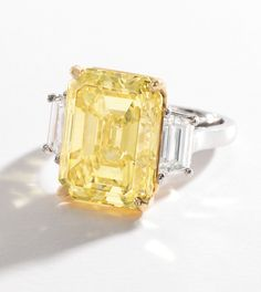 PLATINUM, 18 KARAT GOLD, FANCY INTENSE YELLOW DIAMOND AND DIAMOND RING, VAN CLEEF & ARPELS.  Centered by a cut-cornered rectangular step-cut Fancy Intense Yellow diamond weighing 14.36 carats, flanked by two trapeze-cut diamonds weighing approximately 1.35 carats, size 5¼, signed Van Cleef & Arpels, numbered SU0254.