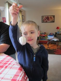 Using a whisk to hold the Easter egg in place to dye it.