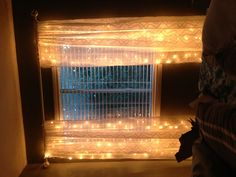 Just string 2 strands of christmas lights up and down behind sheer curtains.  It's inexpensive too!