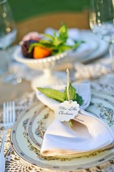 Stacked Cream dishware with gold design and cream napkin with mint tied with name card. #place-settings