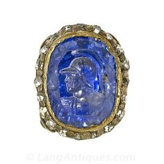 Victorian Intaglio Sapphire Fob: This is a very unusual, Victorian handcarved intaglio Ceylon sapphire fob, depicting the profile of a classic warrior. The ornate fob was designed in silver over gold and contains four old mine-cut diamonds and thirty-six rose-cut diamonds.
